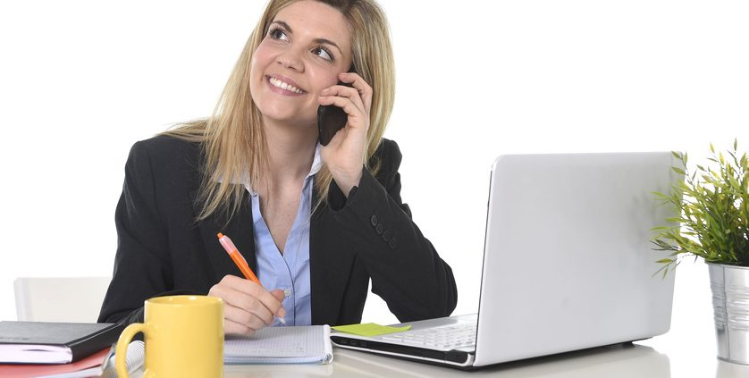 happy Caucasian blond business woman working talking on mobile phone at office computer desk